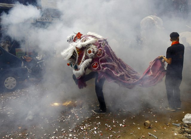 Firecrackers explode as members of the Chinese community perform a lion dance during the Chinese Lunar New Year celebrations in Kolkata February 19, 2015. (Photo by Rupak De Chowdhuri/Reuters)