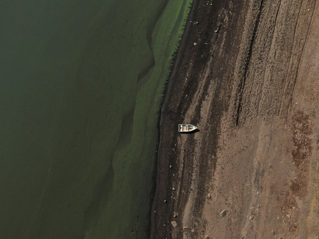 A boat sits idle on the banks of Villa Victoria Dam, the main water supply for Mexico City residents, on the outskirts of Toluca, Mexico, Thursday, April 22, 2021. The mayor of Mexico City said the drought was the worst in 30 years, and that problem can be seen at the series of reservoirs that bring in water from other states to supply the capital. (Photo by Fernando Llano/AP Photo)