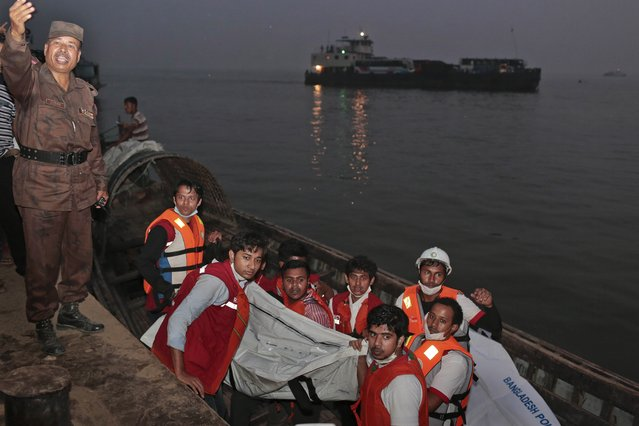 Bangladeshi rescue workers carry the dead body of one of the victims after a river ferry carrying about 100 passengers capsized Sunday after being hit by a cargo vessel,in Manikganj district, about 40 kilometers (25 miles) northwest of Dhaka, Bangladesh, Sunday, February 22, 2015. (Photo by A. M. Ahad/AP Photo)
