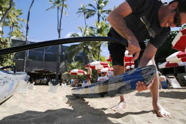 Johnny Puakea, whose father is a well-known craftsman of traditional Koa wood-hewn Hawaiian canoes, assembles one of his own sleek carbon-fiber outrigger canoe designs at the Outrigger Canoe Club in Honolulu, Hawaii January 1, 2016. (Photo by Jonathan Ernst/Reuters)