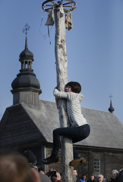 A woman climbs a pole during Maslenitsa celebrations, or Shrovetide, in the village of Ozertso, in outskirts of Minsk, Belarus, Sunday, February 22, 2015. Maslenitsa is a traditional Russian and Belarusian holiday marking the end of winter that dates back to pagan times. (Photo by Sergei Grits/AP Photo)