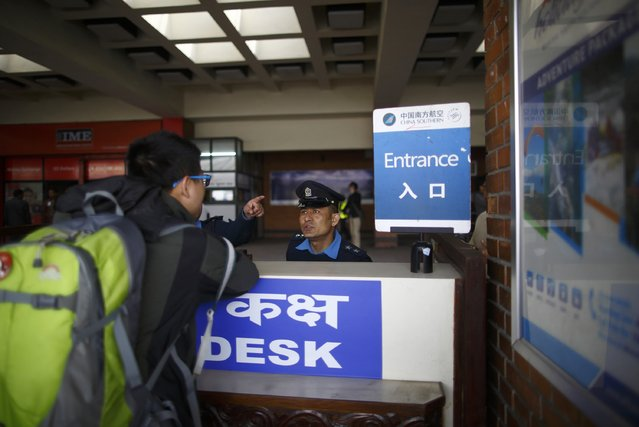 A passenger makes enquires with a Nepalese police officer at an airport help desk when the airport is closed after a Turkish Airlines plane overshot a runway at Tribhuvan International Airport in Kathmandu March 4, 2015. According to local media, all passengers and crew members of the flight were rescued. REUTERS/Navesh Chitrakar