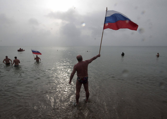 A man waves Russian national flag as he stands in cold waters of the Black Sea during Orthodox Epiphany celebrations in the port city of Yevpatoriya, Crimea, January 19, 2016. Orthodox believers mark Epiphany on January 19 by immersing themselves in icy waters regardless of the weather. (Photo by Pavel Rebrov/Reuters)