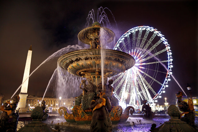 A giant Ferris wheel lights up the night sky for the Christmas holiday season behind a fountain and in front of the Louxor's Obelisque on the Place de la Concorde square in Paris, France, December 11, 2016. (Photo by Charles Platiau/Reuters)