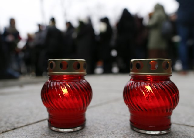 Lit candles are placed on the ground as people gather to attend a memorial service before the funeral of Russian leading opposition figure Boris Nemtsov in Moscow, March 3, 2015. Nemtsov's girlfriend has broken her public silence on the murder of the Russian opposition activist, saying she did not see the killer who gunned him down as they strolled across a bridge near the Kremlin. Anna Duritskaya, who is 23 or 24, said she had been under constant guard since the murder and would probably be unable to attend Nemtsov's funeral on Tuesday. REUTERS/Maxim Shemetov
