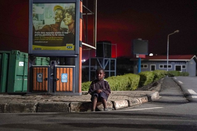 """A lost child sits on a curb as Congolese people flee from Goma, Democratic Republic of Congo (DRC), after the Nyiragongo volcano erupted, at the border point known as """"Petite Barriere"""" in Gisenyi, Rwanda, on May 23, 2021. The government of the Democratic Republic of Congo has ordered the evacuation of the eastern city of Goma after the eruption of Mount Nyiragongo overlooking the border city. The lava reached the city's airport early Sunday, with an official from Virunga National Park – where the volcano is located – telling his staff: """"the situation is deteriorating"""". (Photo by Simon Wohlfahrt/AFP Photo)"""