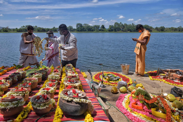 Hindu decorate with flowers over 560 unclaimed clay urns containing ashes of people who died due to Covid-19 coronavirus on the banks of river Cauvery before a mass immersion ritual organised by the government of Karnataka, in Belakavadi Village in Mandya District situated about 125 Km from Bangalore on June 2, 2021. (Photo by Manjunath Kiran/AFP Photo)