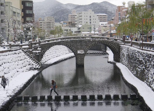 In this Sunday, January 24, 2016 photo, a woman walks on a step-stone bridge in front of Megane Bashi or the Spectacles Bridge, one of the oldest stone bridges in Japan, in snow-covered Nagasaki, southern Japan. Heavy snow in western and central Japan left several people dead in Japan over the weekend. (Photo by Sayaka Takeda/Kyodo News via AP Photo)