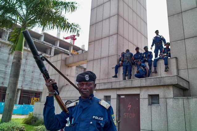 Congolese policemen sit on a monument at the Central Station, in Gombe, Kinshasa, Democratic Republic of Congo, December 19, 2016. (Photo by Robert Carrubba/Reuters)