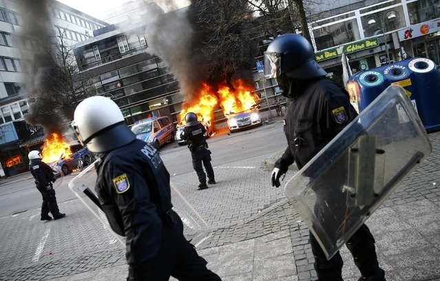 German police cars, set on fire by anti-capitalist protesters, burn near the European Central Bank (ECB) building before the official opening of its new headquarters in Frankfurt March 18, 2015. (Photo by Kai Pfaffenbach/Reuters)
