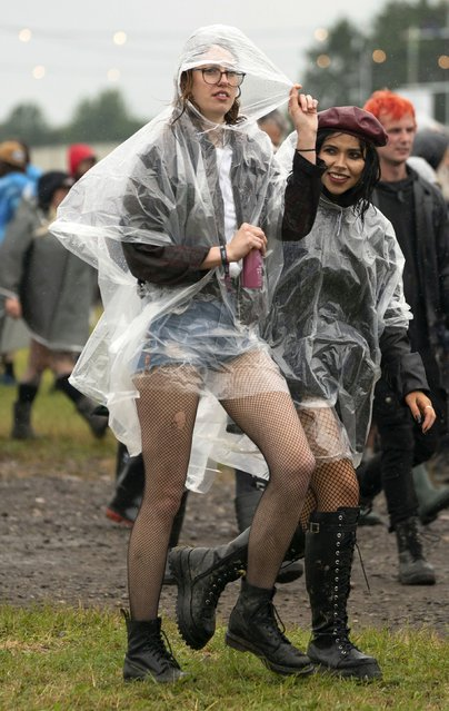 Festivalgoers shelters from the pouring rain on the first day of Download Festival at Donington Park at Castle Donington, England, Friday June 18, 2021. (Photo by Joe Giddens/PA Wire via AP Photo)