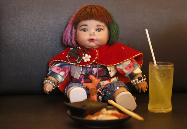 "In this Friday, January 29, 2016 photo, a ""child angel"" doll is offered food by its owner Supavadee Tapmalai at a Japanese restaurant in Bangkok, Thailand. (Photo by Sakchai Lalit/AP Photo)"