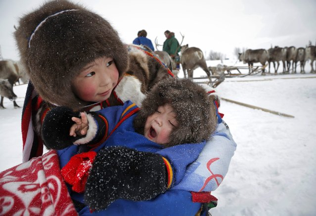 In this photo taken on Sunday, March 15, 2015, Nenets children attend the Reindeer Herder's Day holiday in the city of Nadym, in Yamal-Nenets Region, 2500 kilometers (about 1553 miles) northeast of Moscow, Russia. (Photo by Dmitry Lovetsky/AP Photo)