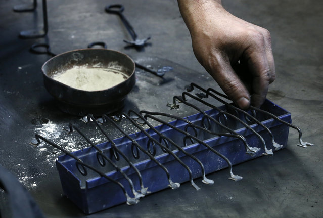 Serge Huguenin of the Blondeau foundry takes a lettering tool during the preparation of a mould for a bell in La Chaux-de-Fonds, Switzerland January 19, 2016. (Photo by Denis Balibouse/Reuters)