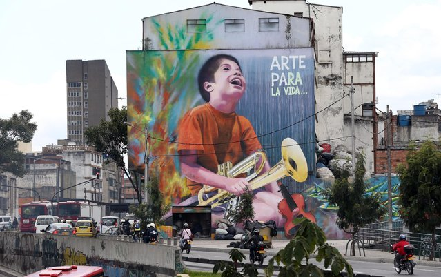 """In this March 13, 2015 photo, a mural of a boy holding an instrument, with a message that reads in Spanish; """"Art for life"""", covers a wall in downtown Bogota, Colombia. Monkeys and butterflies spray-painted in bright colors pay homage to the country's natural beauty and provide welcome relief amid the Andean capital's gray skies and monochromatic red brick architecture. (Photo by Fernando Vergara/AP Photo)"""
