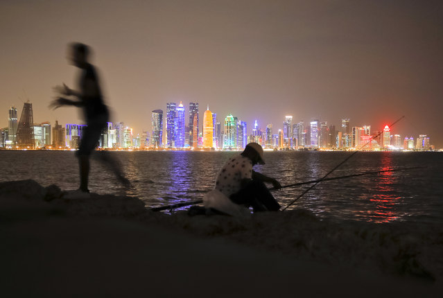 In this November 2, 2018 picture men fish, backdropped by the city skyline Doha, Qatar. Eight stadiums scattered in a 30-mile radius that will host 32 teams from across the planet are in various stages of development, most of them trying to walk the treacherous line of paying homage to the region's history while simultaneously avoiding becoming an expensive and unused relic once the party ends and everyone else goes home. (Photo by Vadim Ghirda/AP Photo)
