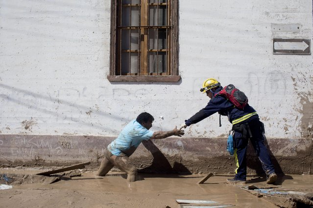 A rescue worker stretches his hand to help a local cross a mud covered street in Chanaral, Chile, Friday, March 27, 2015. Unusually heavy thunder storms, torrential rains and overflowing rivers that began on Tuesday left tons of mud covering communes of northern Chile desert, that left at least nine dead and villages without water, electricity or communications. (Photo by Pablo Sanhueza/AP Photo)