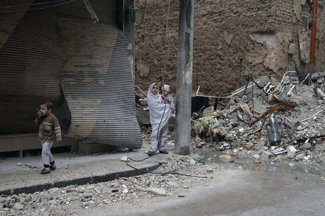 Children walk near rubble in the town of Douma, eastern Ghouta in Damascus November 5, 2015. (Photo by Bassam Khabieh/Reuters)