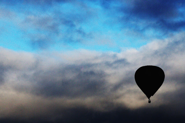 A hot air balloon rises over Innes Common Park during the Balloons over Waikato Festival on March 27, 2015 in Hamilton, New Zealand. Balloon enthusiasts from around New Zealand and the world gather annually for the five-day event in Waikato, NZ. (Photo by Hannah Peters/Getty Images)