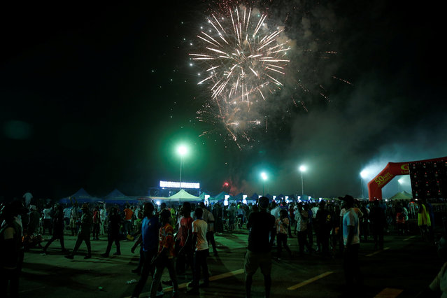 Fireworks are seen as people walk outside the venue of the One Lagos fiesta at the Bar beach in Nigeria's commercial capital Lagos January 1, 2017. (Photo by Akintunde Akinleye/Reuters)