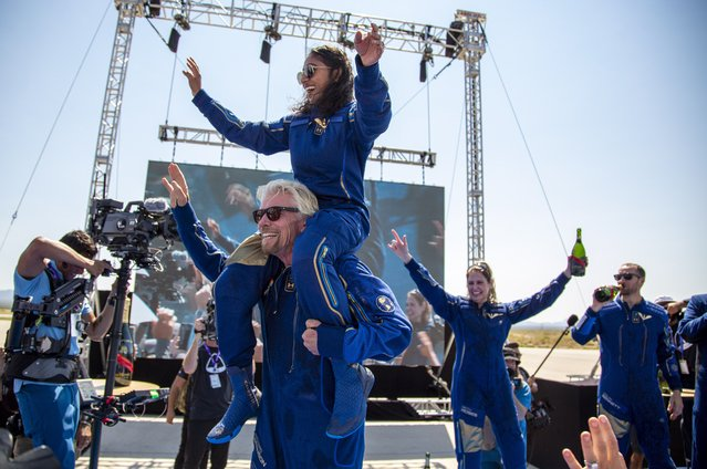 Virgin Galactic founder Richard Branson carries crew member Sirisha Bandla on his shoulders while celebrating their flight to space at Spaceport America near Truth or Consequences, N.M., Sunday, July 11, 2021. (Photo by Andres Leighton/AP Photo)