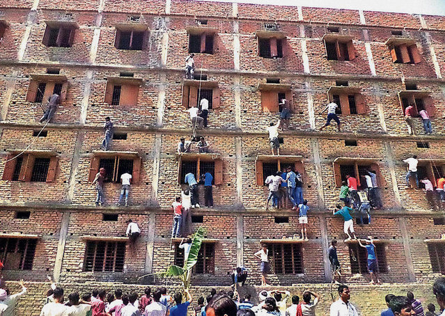 In this Wednesday, March 18, 2014 photo, Indians climb the wall of a building to help students appearing in an examination in Hajipur, in the eastern Indian state of Bihar. Even with police presence, parents and relatives are reported to scale building walls in order to pass notes to help students cheat in their exams. (Photo by AP Photo/Press Trust of India)