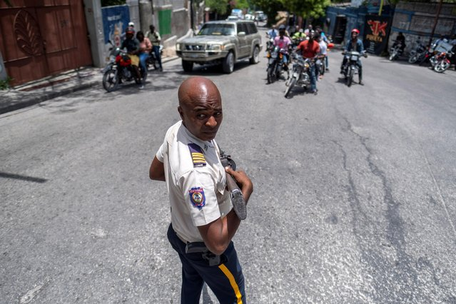 A Haitian National Police officer guards a street in the Petion-Ville neighborhood almost a week after the assassination of President Jovenel Moise, in Port-au-Prince, Haiti on July 13, 2021. (Photo by Ricardo Arduengo/Reuters)