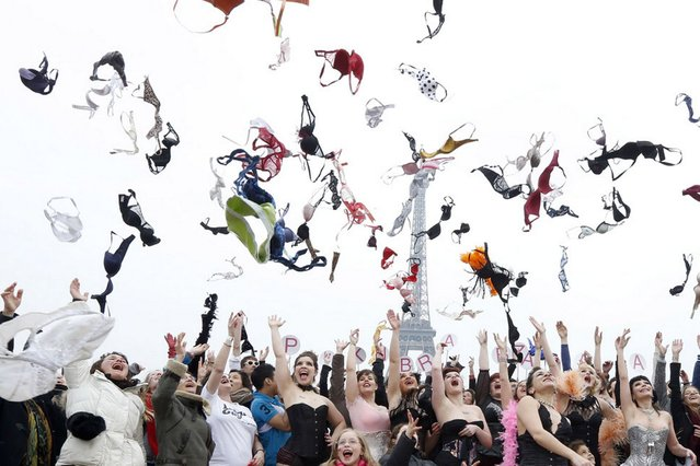 "Woman throws bras on March 25, 2013 at the esplanade des droits de l'homme, in front of the Eiffel tower in Paris, during a happening called by ""Pink Bra Bazzar"", a French organization fighting against and sensitizing on breast cancer. (Photo by Pierre Verdy/AFP Photo)"