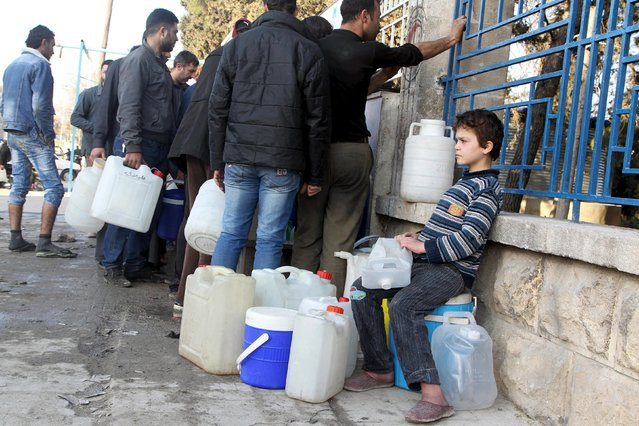 A boy waits to fill water containers while residents wait in line in Bab Neirab, Aleppo, Syria February 15, 2016. (Photo by Abdalrhman Ismail/Reuters)