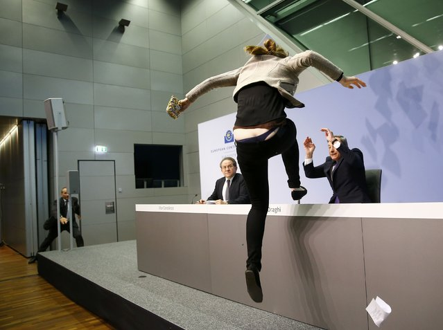 A protester jumps on the table in front of the European Central Bank President Mario Draghi during a news conference in Frankfurt, April 15, 2015. The news conference was disrupted on Wednesday when a woman in a black T-shirt jumped on the podium. (Photo by Kai Pfaffenbach/Reuters)