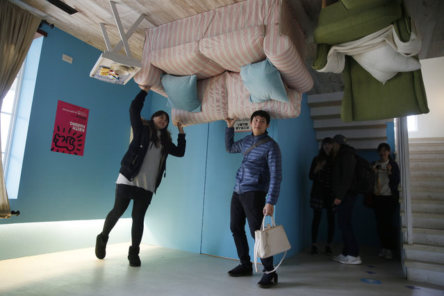 Visitors pose inside an upside-down house created by a group of Taiwanese architects at the Huashan Creative Park in Taipei, Taiwan, Tuesday, February 23, 2016. (Photo by Wally Santana/AP Photo)