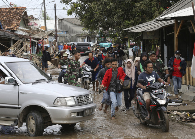 People feared by tsunami run in panic on a street in Sumur village, Indonesia, Tuesday, December 25, 2018. The Christmas holiday was somber with prayers for tsunami victims in the Indonesian region hit by waves that struck without warning Saturday night. (Photo by Achmad Ibrahim/AP Photo)