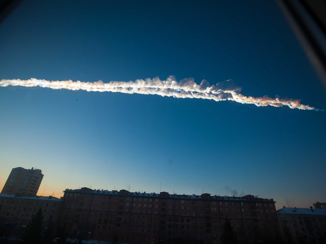 A meteor's trail over the Ural Mountains' city of Chelyabinsk, about 930 miles east of Moscow, Russia, on February 15, 2013. The 13,000 ton meteor hit Earth's atmosphere at 42,000 mph and exploded, smashing windows and causing hundreds of minor injuries. (Photo by Yekaterina Pustynnikova/AP Photo/Chelyabinsk.ru)