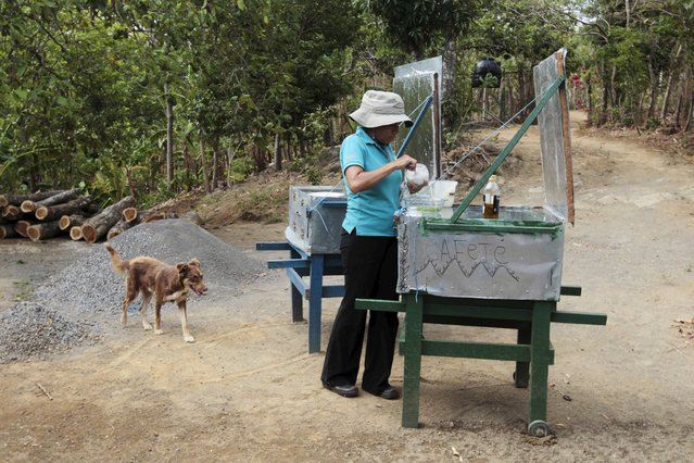 Mercedes Alvarez, who is a member of the Solar Project Foundation for Nicaraguan Women (FUPROSOMUNIC), prepares food in a solar cooker on the outskirts of Masaya city April 15, 2015. The foundation manufactures solar cookers which benefit about 800 women in Nicaragua's agricultural sector. (Photo by Oswaldo Rivas/Reuters)