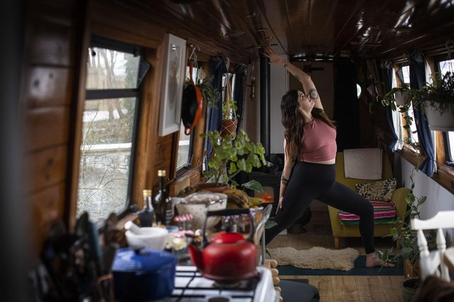 """Yoga teacher Harriet McAtee, who is 6ft tall, performs a """"Viparita Virabhadrasana"""" pose during a class on her 6ft wide narrowboat in Oxford. The Coronavirus pandemic has forced Harriet to conduct her classes via zoom video calls rather than face-to-face as she did pre-pandemic, but she now teaches to people all around the world, with students reaching as far as New Zealand. Issue date: Thursday February 18, 2021. (Photo by Victoria Jones/PA Images via Getty Images)"""