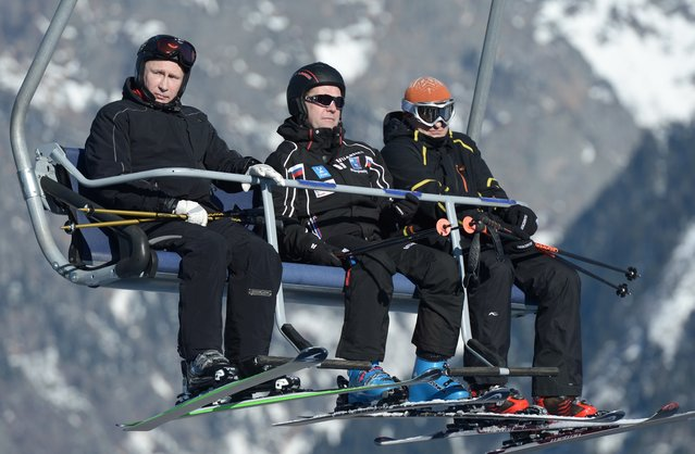 Russian Prime Minister Dmitry Medvedev, centre, and President Vladimir Putin, left,  look around whilst sitting on a ski lift at the mountain resort of Krasnaya Polyana near the Black Sea resort of Sochi, southern Russia, Friday, January 3, 2014. Other person in photo is unidentified by source. (Photo by Alexei Nikolsky/AP Photo/RIA-Novosti/Presidential Press Service)
