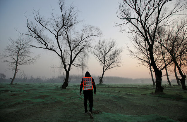 Artist Liu Bolin wearing a vest with 24 mobile phones walks in smog as he live broadcasts air pollution in the city on the fourth day after a red alert was issued for heavy air pollution in Beijing, China, December 19, 2016. (Photo by Jason Lee/Reuters)