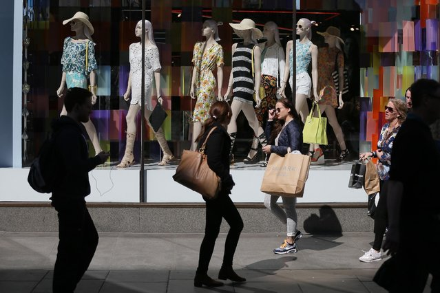 Shoppers walk past a store on Oxford Street in London, Tuesday, April 14, 2015. (Photo by Tim Ireland/AP Photo)