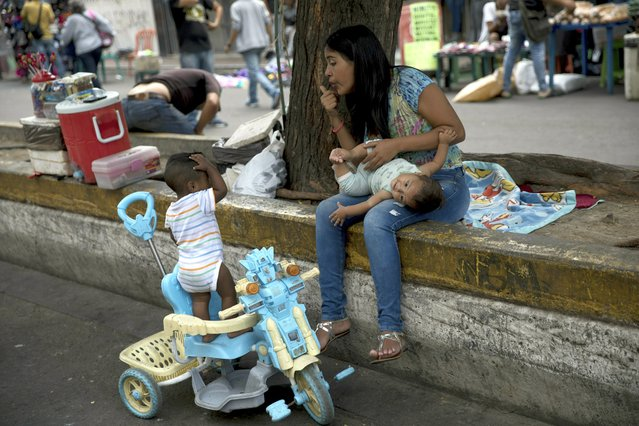 A woman with two children stops prior to crossing the Simon Bolivar International bridge into Colombia, in San Antonio del Tachira, Venezuela, Thursday, February 21, 2019. Opposition leaders led by self-proclaimed interim president Juan Guaido are vowing to bring in U.S. supplies of emergency food and medicine to dramatize the country's hardships under President Nicolas Maduro, who has said the country doesn't need such help. (Photo by Rodrigo Abd/AP Photo)