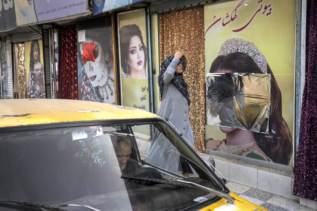 A woman walks past beauty salons with window decorations which have been defaced in Kabul, Afghanistan, Sunday, September 12, 2021. Since the Taliban gained control of Kabul, several images depicting women outside beauty salons have been removed or covered up. (Photo by Bernat Armangue/AP Photo)