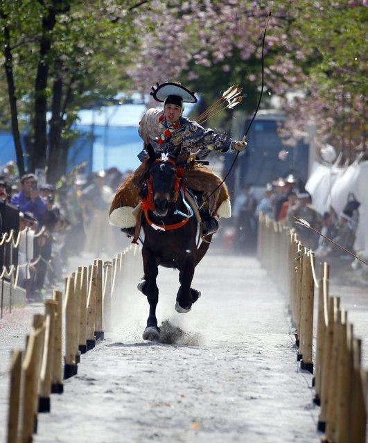An archer in a samurai warrior costume aims at a target in the Asakusa Yabusame horseback archery event at Sumida Park in Tokyo, Saturday, April 18, 2015. (Photo by Shizuo Kambayashi/AP Photo)