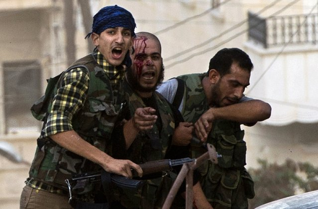 An injured rebel fighter is helped away during heavy fighting with Syrian government troops some 50 meters away in Aleppo's northern Izaa quarter on September 27, 2012. (Photo by Miguel Medina/AFP Photo)
