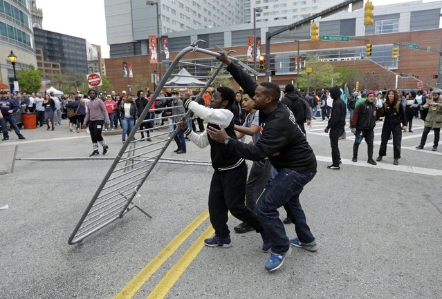 Protestors prepare to throw a barricade at a bar near Oriole Park at Camden Yards after a rally for Freddie Gray, Saturday, April 25, 2015, in Baltimore. (Photo by Patrick Semansky/AP Photo)