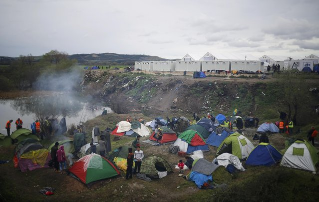 Migrants stand outside their tents at a makeshift camp on the Greek-Macedonian border near the village of Idomeni, Greece March 10, 2016. (Photo by Stoyan Nenov/Reuters)