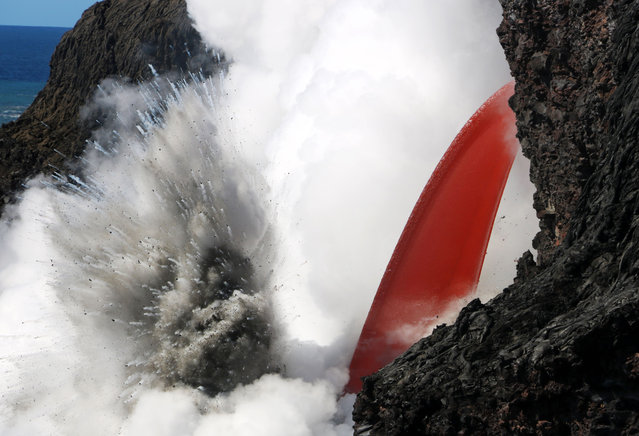This image obtained January 31, 2017 from the US Geological Survey's Hawaiian Volcano Observatory showing a  lava stream, pouring out of the lava tube on the sea cliff at the Kamokuna ocean entry from the Kilauea Volcano on January 29. (Photo by AFP Photo/USGS)