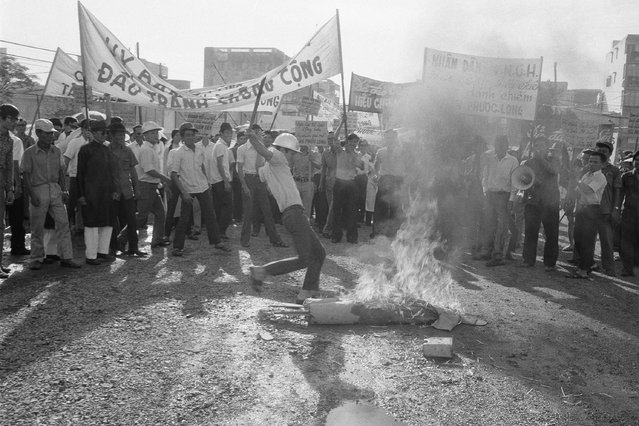 Anticommunist demonstrator kicks burning effigy of Viet Cong soldier during unruly protest outside Saigon headquarters of International Commission of Control and Supervision in Saigon, Jan. 6, 1975. About a hundred demonstrators protested fierce fighting in Phuoc Long province in violation of the Paris peace agreement, which the ICCS is charged with enforcing. (Photo by AP Photo)