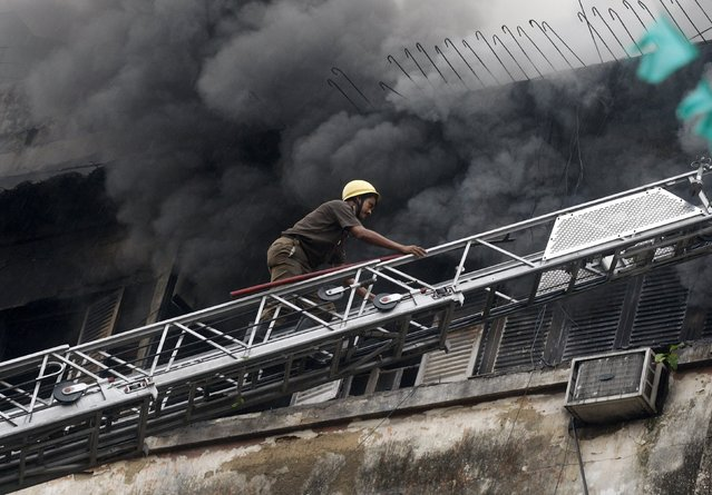 A firefighter climbs up a ladder to douse a fire that broke out in a shopping mall in Kolkata, India, April 26, 2015. (Photo by Rupak De Chowdhuri/Reuters)