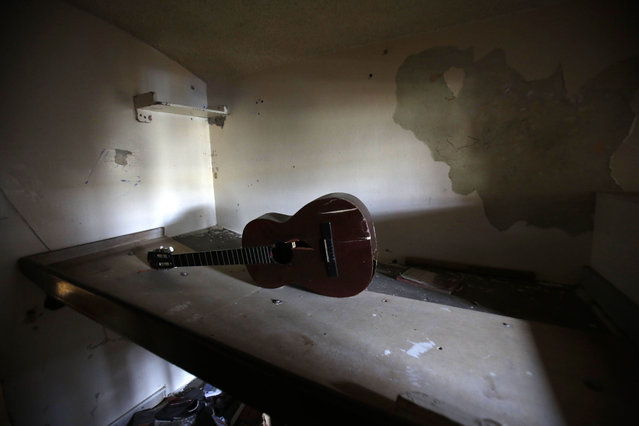 This April 9, 2015 photo shows a broken guitar left behind in a cell at the now empty Garcia Moreno Prison, during a guided tour for the public in Quito, Ecuador. Clothes, a guitar and other belongings were left behind by departing inmates who were transferred to a newer facility. (Photo by Dolores Ochoa/AP Photo)