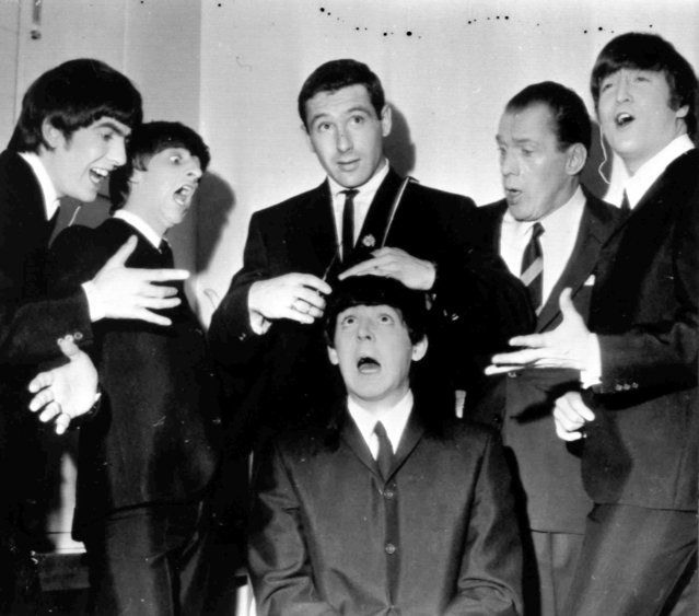 American speed skating champion Terry McDermott, top centre,a barber by trade, prepares to take a swipe at the famed locks of Beatle Paul McCartney, seated, to the mock horror of the other Beatles and TV host Ed Sullivan, during rehearsals at the TV Studio, New York, February 9, 1964. From left, George Harrison, Ringo Starr, McDermott, Ed Sullivan and John Lennon. (Photo by AP Photo)
