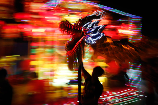 Performers take part in a dragon dance during a night parade to celebrate Chinese New Year in Kuala Lumpur, Malaysia, Sunday, February 9, 2014. The Lunar New Year this year marks the Year of the Horse in the Chinese calendar. (Photo by Vincent Thian/AP Photo)